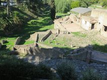 View of some Pompeii ruins. Pompeii, Italy - October 14, 2017: Ruins of Courtyards and walls in grassy fields royalty free stock image