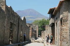 Pompeii ruins. The ruins of Pompeii with tourists and the Mount Vesuvius in the distance Royalty Free Stock Photography