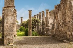 Pompeii ruins: a yard and destroyed stone columns at archeological site. Pompeii ruins: tree and columns in a yard. Remains of the ancient Pompeii town destroyed royalty free stock images