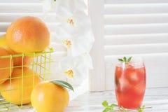 Pompelmi e vetro freschi del succo di pompelmo con ghiaccio sulla tavola di legno bianca rustica di fronte ai ciechi immagine stock