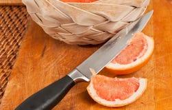 Pompelmo affettato con il coltello tagliente ed il canestro tessuto immagini stock