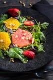 Pompelmo ed insalata arancio della miscela con i pinoli sulla banda nera e sul fondo scuro, composizione verticale fotografia stock libera da diritti