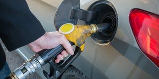 Pompend gas dicht omhoog van mensen pompende brandstof in auto bij benzinestation stock afbeelding