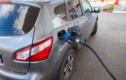 Pompende benzinebrandstof in personenauto bij benzinestation royalty-vrije stock afbeeldingen