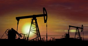 Pompes à huile - extraction de l'huile sur le fond de coucher du soleil photographie stock libre de droits