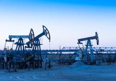 Pompes à huile sur un gisement de pétrole photographie stock