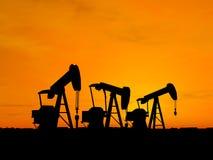 Pompes de pétrole de la silhouette trois Images stock
