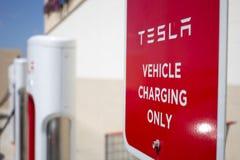 Pompes de station de charge de Tesla et signe indiqué photos libres de droits