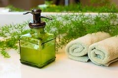 Pompez la bouteille avec du savon liquide, des serviettes et des verts sur le coun de salle de bains Images stock