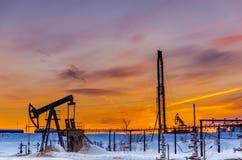 Pompez la plate-forme de cric, de tête de puits, de canalisation et pétrolière pendant le coucher du soleil Photos libres de droits