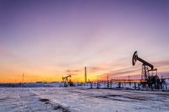 Pompez la plate-forme de cric, de tête de puits, de canalisation et pétrolière pendant le coucher du soleil Photographie stock libre de droits