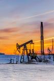 Pompez le cric, la tête de puits et la plate-forme pétrolière pendant le coucher du soleil Photographie stock libre de droits