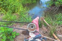 Pompi l'acqua dal canale alle risaie Fotografia Stock