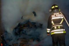Pompier au travail dedans au feu images stock