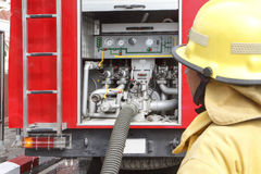 Pompier avec le camion de pompiers Photographie stock libre de droits