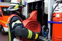Pompier avec le tuyau de l'eau sur un firetruck Photos libres de droits