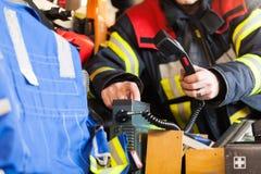 Pompier dans une étincelle de camion de pompiers avec le poste radio Photo libre de droits