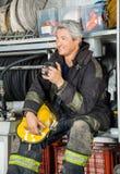 Pompier de sourire s'asseyant dans le camion à la caserne de pompiers Images stock