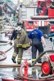 Pompier et sauveteur marchant loin construisant dans les gouttes de l'eau après avoir éteint Image stock