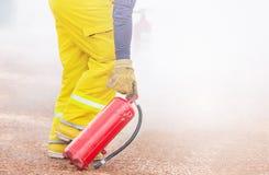 Pompier professionnel en feu de combat de pompier d'uniforme d'extincteur jaune de participation photographie stock libre de droits
