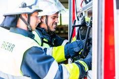 Pompier vérifiant les tuyaux à la pompe à incendie photographie stock