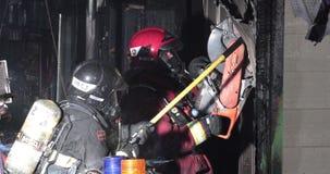 Pompiere che per mezzo di una sega rotatoria di salvataggio archivi video