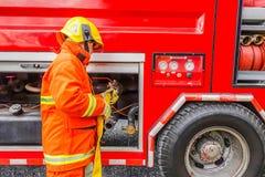 Pompiere che tiene il tubo flessibile dell'acqua vicino al camion con attrezzatura fotografia stock