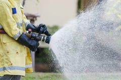 Pompiere che tiene l'ugello ad alta pressione della manichetta antincendio Fotografia Stock