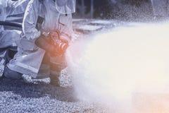 Pompiere che tiene l'ugello ad alta pressione della manichetta antincendio Immagini Stock