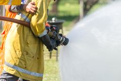Pompiere che tiene l'ugello ad alta pressione della manichetta antincendio Fotografie Stock