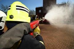Pompiere con il tubo flessibile ad alta pressione della LANCIA PYRO Fotografie Stock