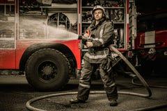Pompiere con il tubo flessibile dell'acqua vicino al camion immagine stock