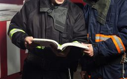 Pompiere del vigile del fuoco nell'azione che sta vicino ad un firetruck EMER Immagini Stock