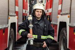 Pompiere del vigile del fuoco nell'azione che sta vicino ad un firetruck EMER Fotografie Stock Libere da Diritti