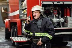 Pompiere del vigile del fuoco nell'azione che sta vicino ad un firetruck EMER Fotografia Stock