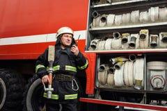 Pompiere del vigile del fuoco nell'azione che sta vicino ad un firetruck EMER Immagini Stock Libere da Diritti