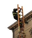 Pompiere di Fearess sopra un'alta scala di legno durante il salvataggio Immagini Stock Libere da Diritti