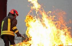 Pompiere durante l'esercizio di allenamento fuori da un fuoco enorme nel Br Fotografie Stock