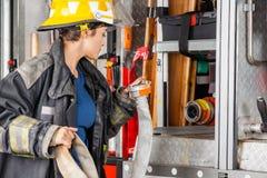 Pompiere Examining Water Hose in camion immagine stock libera da diritti