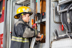 Pompiere femminile Fixing Water Hose in camion fotografia stock libera da diritti