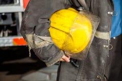 Pompiere femminile Holding Yellow Helmet immagine stock