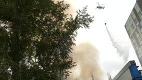 Pompiere Helicopter Drops Water per estinguere un fuoco su una costruzione video d archivio