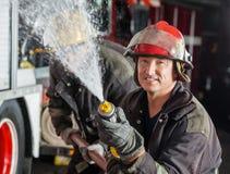 Pompiere Spraying Water While che pratica con fotografia stock libera da diritti