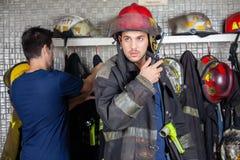 Pompiere Using Walkie Talkie con il collega nel fondo fotografia stock libera da diritti