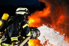 Pompiere - vigili del fuoco che estinguono una grande fiammata Fotografie Stock Libere da Diritti