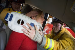 Pompieri che aiutano una donna danneggiata in un'automobile Immagine Stock