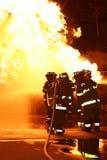 Pompieri che attacano Flames-2 Immagine Stock