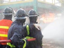 Pompieri che combattono fuoco con acqua fatta pressione su durante l'esercizio di allenamento Fotografie Stock