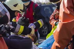 Pompieri che curano una persona danneggiata Immagini Stock Libere da Diritti