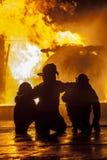 Pompieri che guardano un fuoco bruciare Immagini Stock
